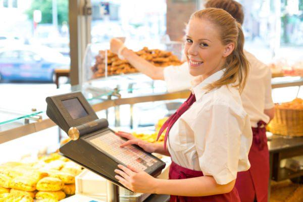 Cashier In Baker's Shop Posing With Cash Register - FINTT - Inteligência Financeira e Contábil